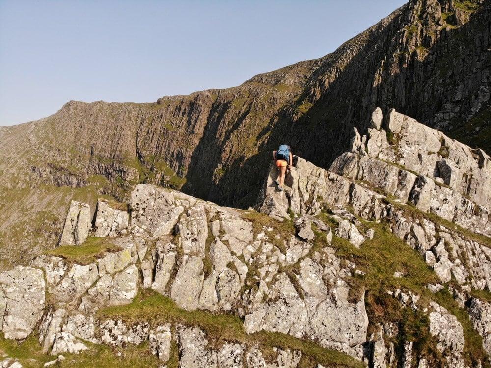Female hiker scrambling over rocks