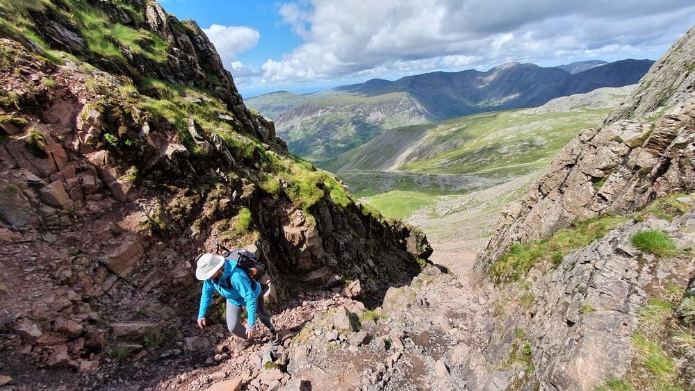 Hiker scrambling up the mountain